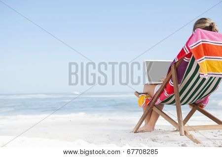 Woman sitting on beach in deck chair using laptop on a sunny day