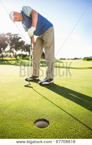 Golfer standing on the putting green watching hole on a sunny day at the golf course