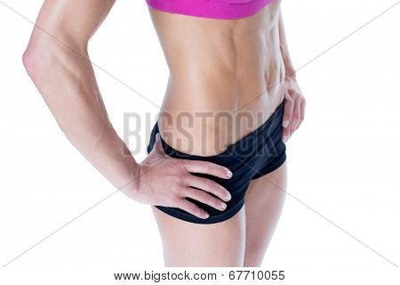 Female bodybuilder posing in pink sports bra and shorts mid section on white background