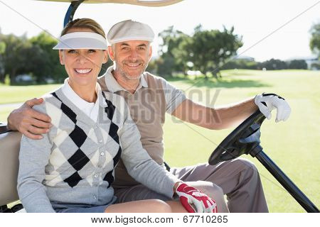 Happy golfing couple driving in their buggy smiling at camera on a sunny day at the golf course