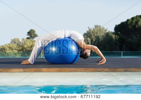 Peaceful brunette in cobra pose over exercise ball poolside on a sunny day at the spa