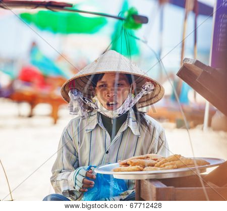 PHU QUOC, VIETNAM - APRIL 26, 2014: Vietnamese woman in traditional headdress, which protects from the sun offers fruits for sale to tourists at Long beach on Phu Quoc island, Vietnam.