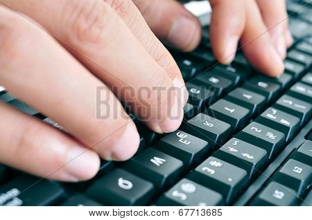 closeup of the hands of a man typing on a computer keyboard