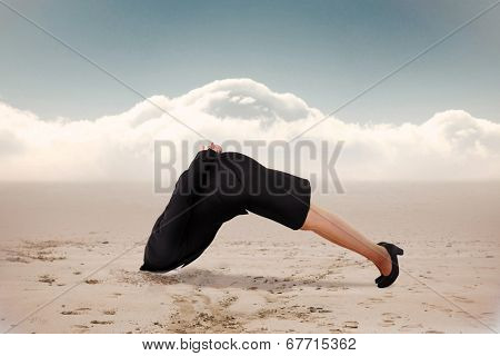 Businesswoman burying her head against cloudy sky background