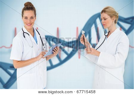 Composite image of female medical team against blue medical background with dna and ecg