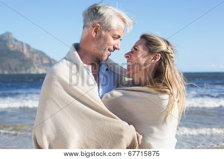 Smiling couple wrapped up in blanket on the beach on a sunny day