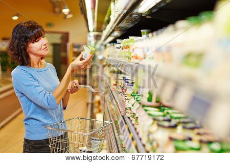 Elderly woman with shopping cart buying yogurt in supermarket