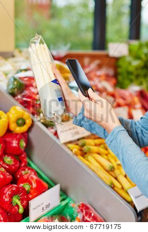 Customer in supermarket scanning barcode of a package asparagus with his smartphone