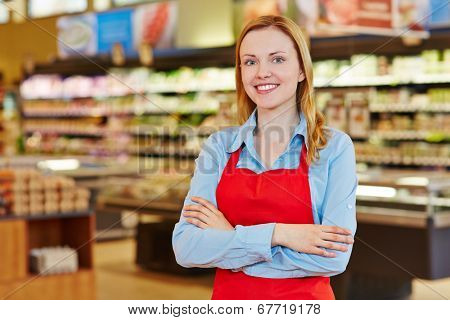 Young happy saleswoman with red apron in a supermarket