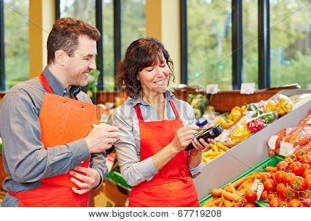 Staff in supermarket using mobile data acquisition terminal for vegetables delivery