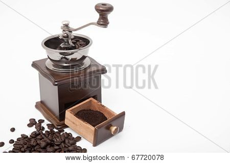 Isolated Vintage Coffee Bean Grinder And Fresh Ground Coffee