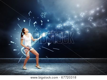 Young girl in shorts playing on imaginary guitar