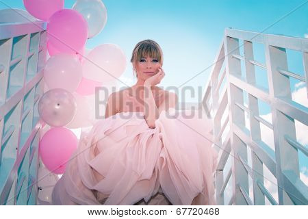 young beautiful woman in elegant wedding dress hold balloons sitting on  white stairs against blue sky