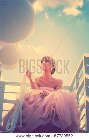 young beautiful woman in elegant wedding dress hold balloons sitting on  white stairs against sky with clouds, retro colors