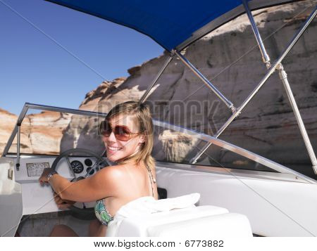 Young Woman Smiling And Driving Boat