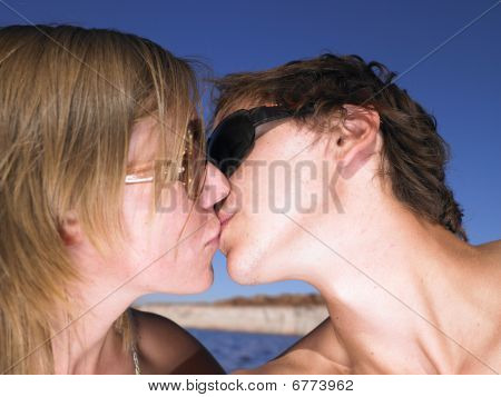 Young Man In Sunglasses Kissing Woman