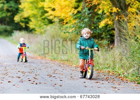 Active Twin Boys Driving On Bikes In Autumn Forest