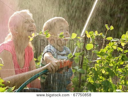 Mother and her young son playing with water