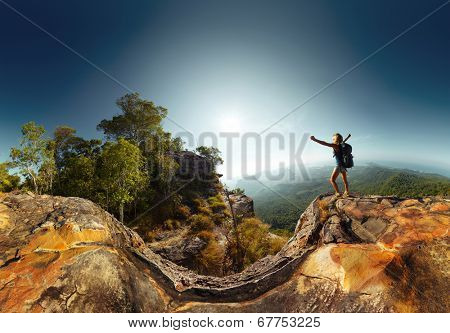 Hiker standing on top of the mountain with raised hand