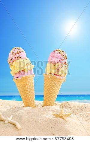 Two ice cream cones stuck in the sand on a sunny beach