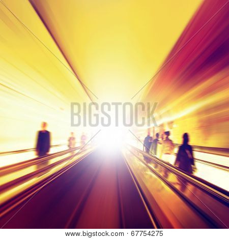 Abstract image of moving walkway and blurred people.