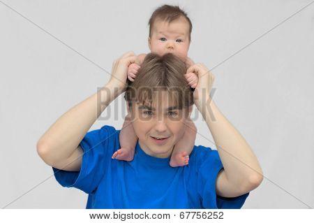 Newborn baby child on the neck of daddy
