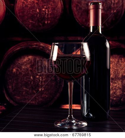 Red Wine Glass Near Bottle On Wood Table And In Old Wine Cellar Background