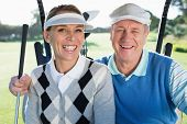 foto of buggy  - Happy golfing couple sitting in golf buggy smiling at camera on a sunny day at the golf course - JPG
