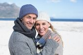 picture of cold-shoulder  - Attractive couple smiling at camera on the beach in warm clothing on a bright but cool day - JPG
