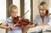stock photo of violin  - Young boy playing violin in music lesson - JPG