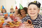 stock photo of tarts  - Young children eating jam tarts at birthday party - JPG