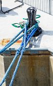 stock photo of bollard  - Frayed blue rope looped around an old black bollard on pier - JPG