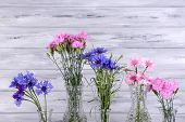 Beautiful summer flowers in vases on grey wooden background pic.