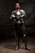 foto of reign  - Medieval Knight posing with sword  and helmet in a dark stone background. Full-length portrait.
