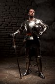 stock photo of reign  - Medieval Knight posing with sword  and helmet in a dark stone background - JPG