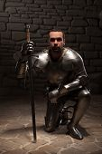 pic of kneeling  - Medieval knight  kneeling with sword on a dark stone wall background - JPG