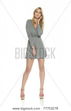 Young Beautiful woman wearing a gray dress isolated on a white background
