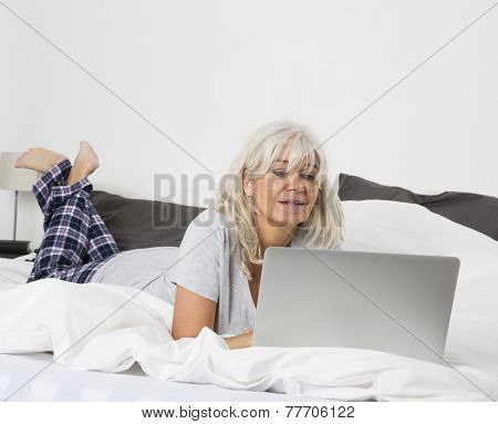 Mid age woman with a laptop lying down in bed