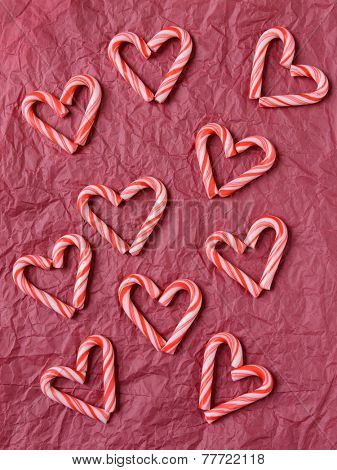Overhead shot of mini candy canes forming heart shapes on a red tissue paper background. Vertical format.