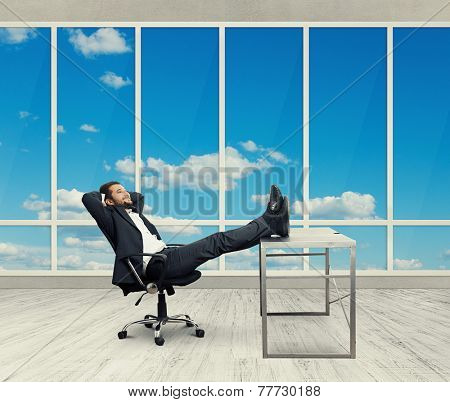 young businessman put his feet up on the table, resting and smiling in the light office with big windows