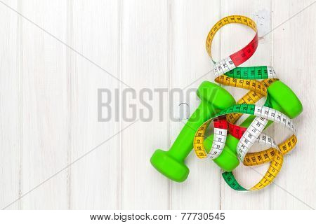 Dumbells and tape measure over wooden background with copy space. Fitness and health