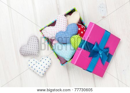 Gift box with valentines day toy hearts on white wooden table background