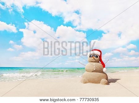 Sandy Snowman In Santa Hat On Sea Beach. New Years And Christmas Holidays Concept