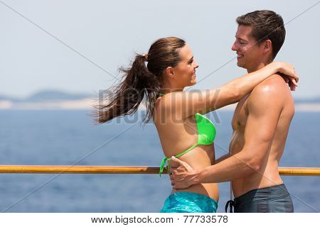 romantic couple in swimsuits hugging on cruise ship