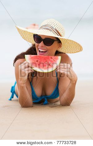 cheerful young woman eating watermelon on beach