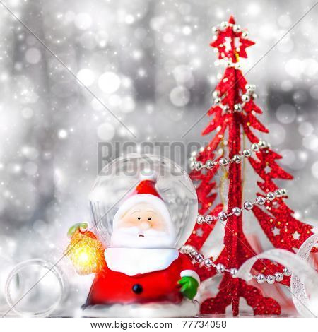 Beautiful Christmas still life, cute Santa Claus toy with little decorative red christmas tree on silver blurry background, beauty of winter holidays concept
