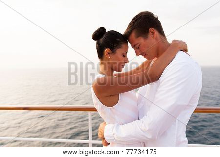 beautiful young couple hugging with eyes closed on a cruise ship