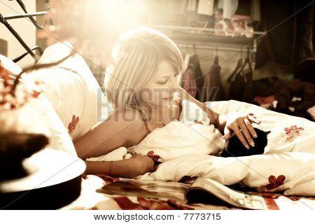 Menina na cama, lendo uma revista e afaga o gato