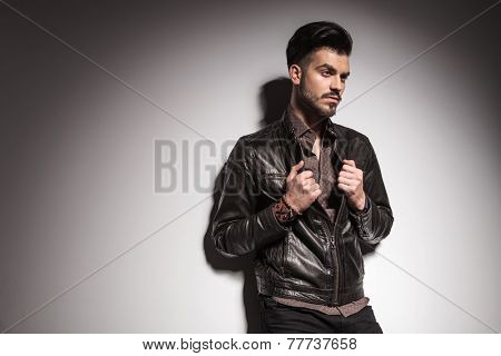 Side view image of a handsome young fashion man fixing his jacket while looking away from the camera.