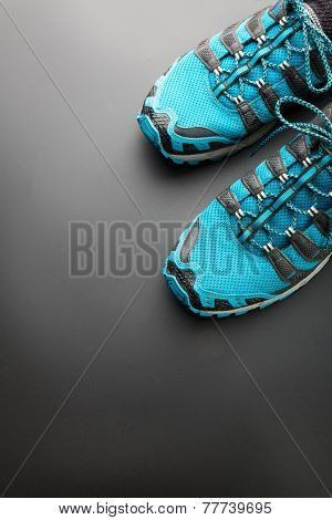 Blue running shoes on grey